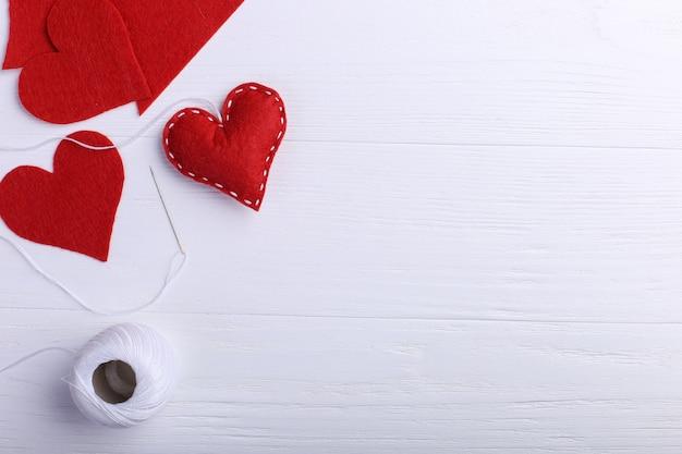 Handgemaakt rood vilthart naast draden en een naald op een witte tafel. vrouwendag concept, kopie ruimte.