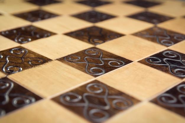 Handgemaakt schaakbord, close-up, zijaanzicht, mooie tekening op hout
