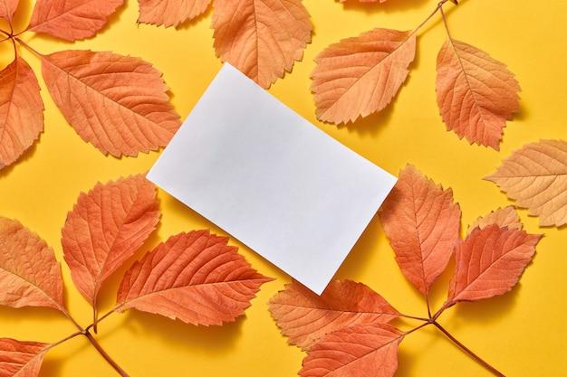 Handgemaakt wenskaart witboek blad op een kleurrijke herfstbladeren op een gele achtergrond met kopieerruimte. plat leggen.