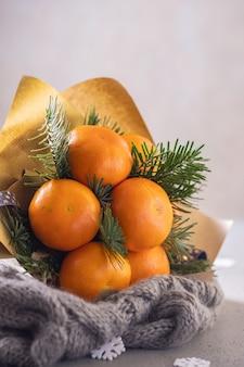 Handgemaakt winterfruitboeket van mandarijn en kerstboomtakken