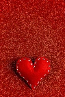 Handgemaakt zacht gestikt vilten hart op een rode glanzende pailletten in de zijkant. het concept voor valentijnsdag.