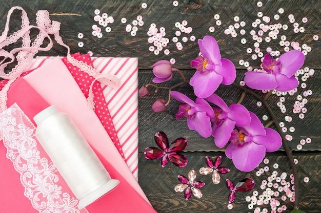Handgemaakte accessoires. katoen stof, kant, spoeldraad, kristallen en pailletten voor handwerk op oude houten achtergrond. orchideebloemen.