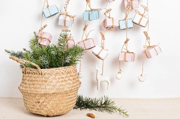 Handgemaakte adventskalender met geschenkdozen aan touwen en dennennaalden in rieten mand