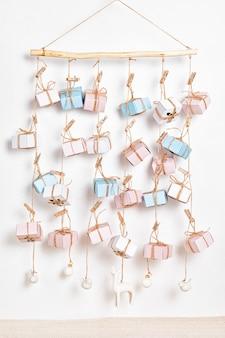 Handgemaakte adventskalender met geschenkdozen die aan touwen hangen