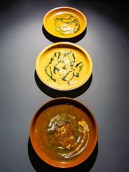 Handgemaakte borden van dagestan meesters aan de muur. onderaanzicht, bovenverlichting