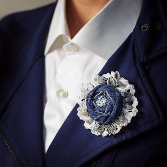 Handgemaakte broche in de vorm van een bloem gemaakt van denim op witte kanten stof