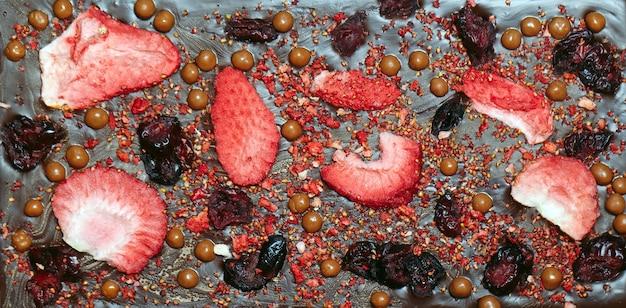 Handgemaakte chocoladerepen met vulling van aardbeien en noten.