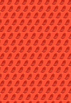 Handgemaakte decoratieve achtergrond met organische herfstrode kleurbladeren op koraalpapier. verticale achtergrond voor uw creativiteit.