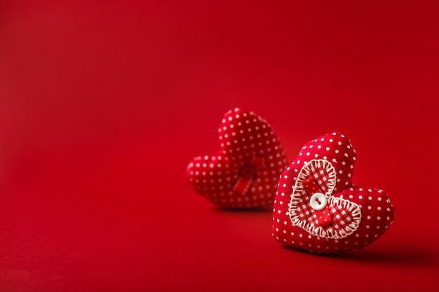 Handgemaakte decoratieve stoffenharten voor valentijnsdag op rode backround