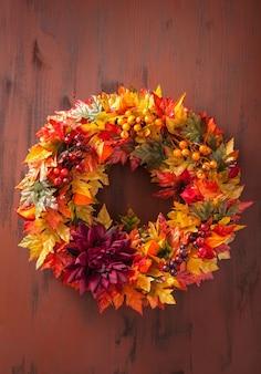 Handgemaakte diy kunstmatige herfstkrans decoratie met bladeren bessen bloem