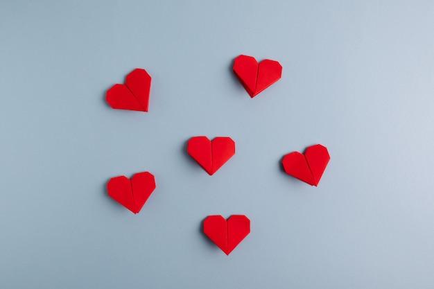 Handgemaakte diy rode origami harten op een blauwe tafel