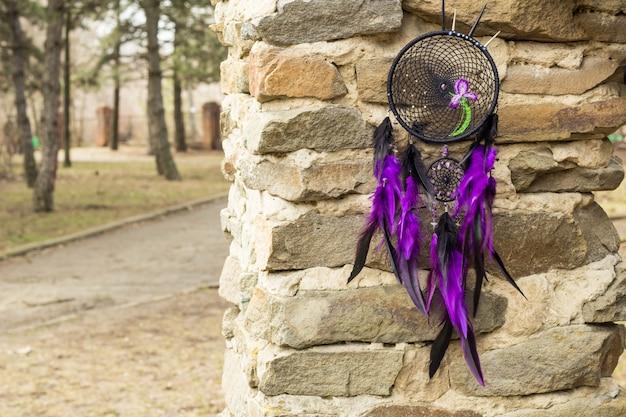 Handgemaakte dromenvanger met veren, draden en kralen touw hangend