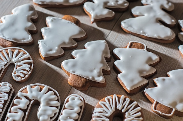 Handgemaakte feestelijke peperkoekkoekjes in de vorm van sterren, personeel, kerstbomen. op een licht aanrecht.
