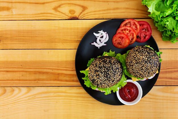 Handgemaakte hamburger op donkere ondergrond. heerlijke zwarte burger