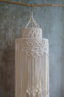 Handgemaakte katoenen macramé lampenkap in woonkamer over betonnen muur, hangend aan een droge tak