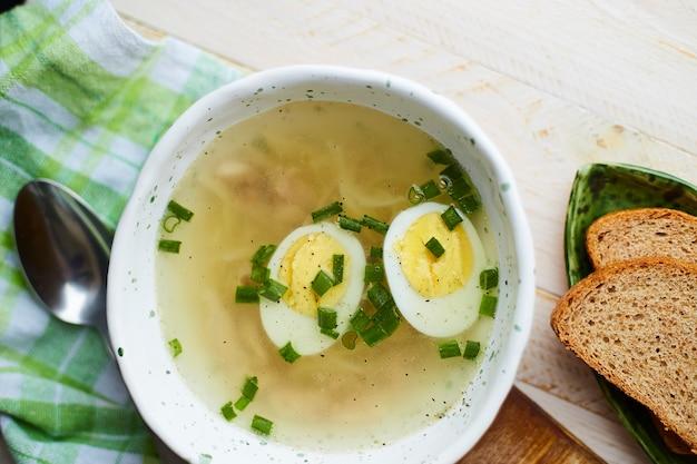 Handgemaakte keramische kom met kippensoep, gekookte eieren en verse groene ui op een tafel