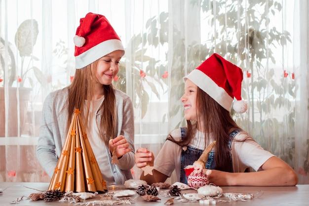 Handgemaakte kerst. de meisjes lachen en staan op het punt een zelfgemaakte kerstboom te versieren met houten speelgoed
