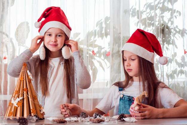Handgemaakte kerst. de meisjes versieren de papieren boom en halen de versieringen uit elkaar.