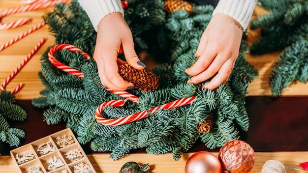 Handgemaakte kerst interieurdecoratie. close-up van vrouwelijke bloemisthanden die groen sparrentakje, suikergoedriet gebruiken om krans te creëren.