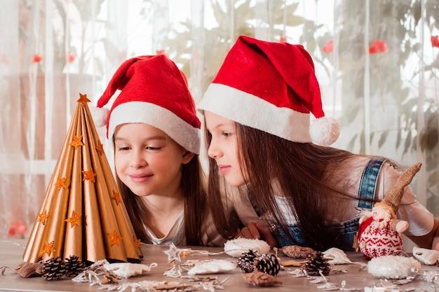 Handgemaakte kerst. meisjes bewonderen een zelfgemaakte papieren boom