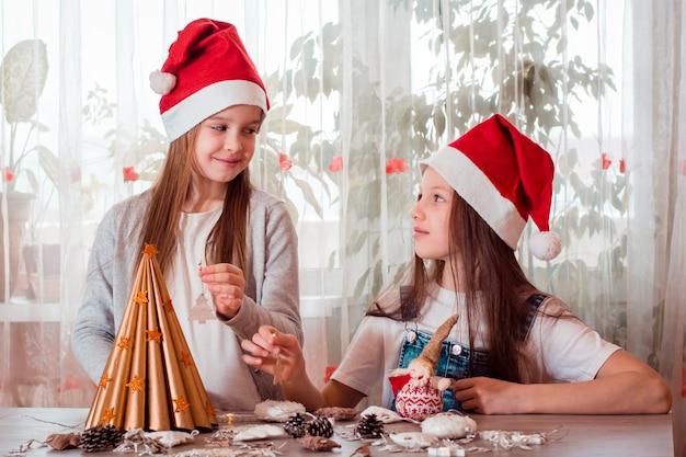Handgemaakte kerst. meisjes gaan een zelfgemaakte kerstboom versieren met houten speelgoed