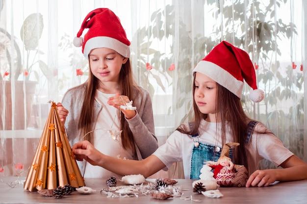 Handgemaakte kerst. meisjes lijmen sterren op een boom van handgeschept papier en maken een krans