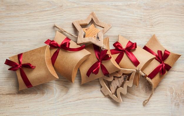 Handgemaakte kerstcadeaus van kraftpapier en houten speelgoed op de kerstboom