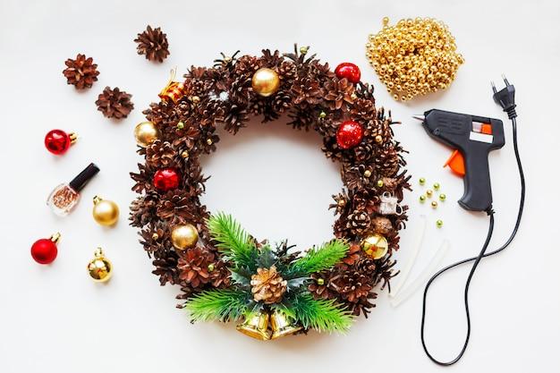 Handgemaakte kerstkrans en dingen die je nodig hebt om er dennenappels, glitter, decoratieve ballen en kralen, lijmpistool van te maken.