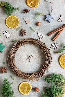 Handgemaakte kerstkrans met houten kerstspeelgoed, gedroogde stukjes sinaasappel en kruiden