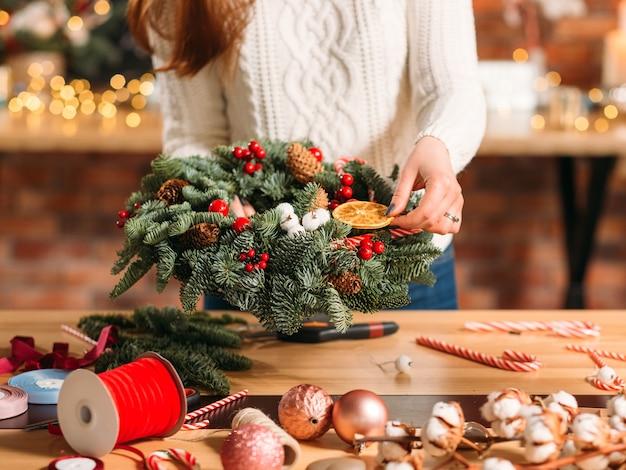 Handgemaakte kerstkrans. vrouwelijke bloemist met winterdecoratie.