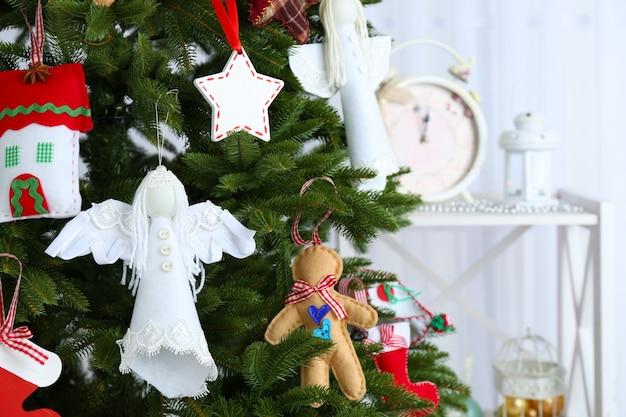 Handgemaakte kerstversieringen op kerstboom op lichte ondergrond
