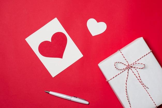 Handgemaakte kleine geschenkdoos met hartsymbool op rode achtergrond.