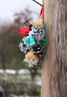 Handgemaakte kleine kerstkrans die buiten op de achtergrond van de winteraard hangt