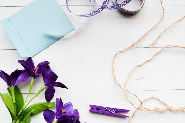 Handgemaakte kunstmatige paarse bloemen; papier; lint; wasknijper en string op witte plank achtergrond