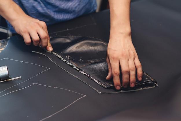 Handgemaakte lederen vakman. werknemer naaien leerproduct. leerwerkplaats. man met crafting tool en werken, close-up. dingen met de hand maken. werkproces van het naaien van autostoelhoes.