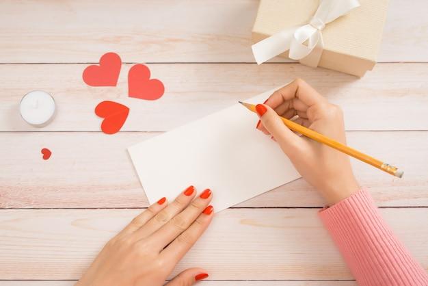 Handgemaakte liefdeskaart voor valentijnsdag op houten achtergrond.