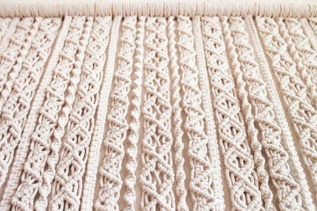 Handgemaakte macrame 100 katoenen wanddecoratie met houten stok hangend aan een witte muur macrame vlechtwerk en katoenen draden eco vriendelijk natuurlijk decoratieconcept in het interieur