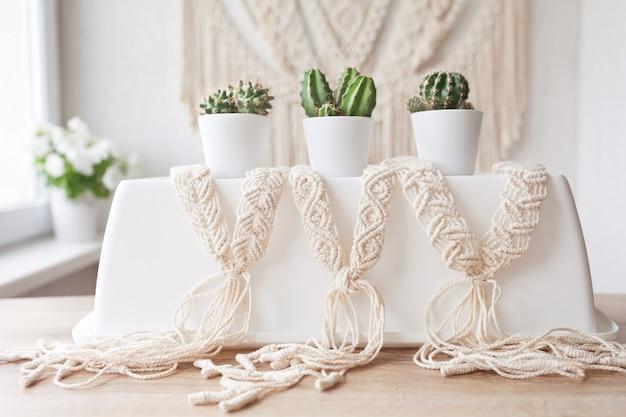 Handgemaakte macrame close-up. natuurlijke katoenen draden. stijlvolle riem voor dameskleding. vrouwelijke hobby. eco-vriendelijk modern breien diy natuurlijk decoratieconcept.