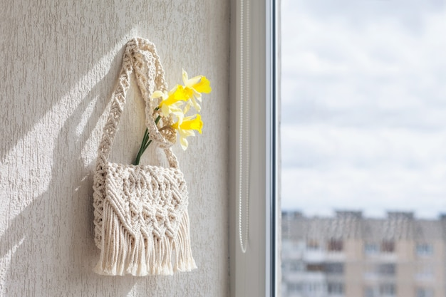 Handgemaakte macramé tas aan de lichte muur.