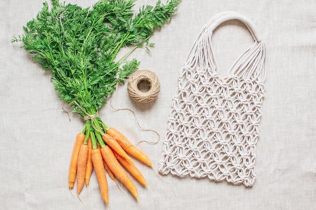 Handgemaakte macrame-tas met verse wortelen op het linnen