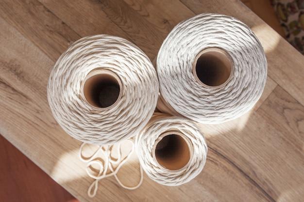 Handgemaakte macrame vlechten en katoenen draden op rustieke houten tafel. hobby breien katoenen draadspoel op een houten bord. vrouwelijke hobby. top uitzicht