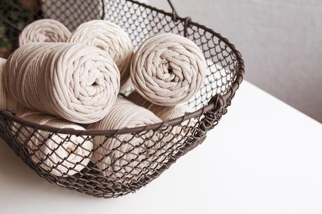 Handgemaakte macramé vlechten en natuurlijke katoenen draden in een mand op een witte achtergrond met schaduwen