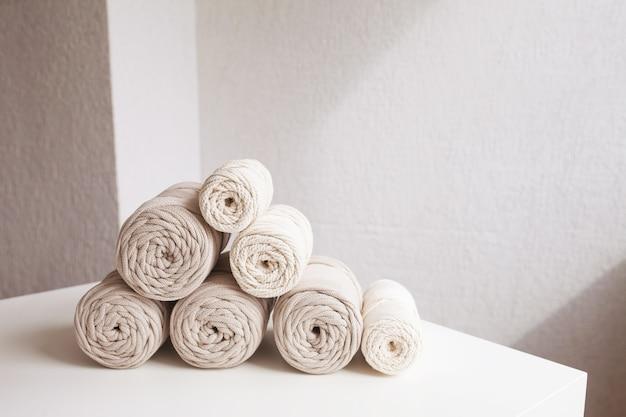Handgemaakte macramé vlechten en natuurlijke katoenen draden stapelen zich op een witte achtergrond met schaduwen