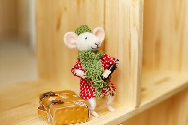 Handgemaakte mohair knuffel. voelde rat met een fles wijn in zijn handen en een gele koffer ernaast