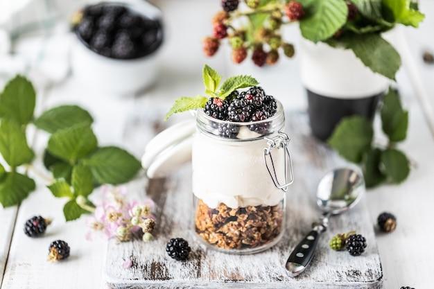Handgemaakte muesli met witte natuurlijke yoghurt met bramen in een glazen transparante pot