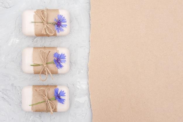 Handgemaakte natuurlijke zeep set grens versierd met ambachtelijk papier, plaag en blauwe korenbloemen op grijze stenen achtergrond plat lag kopie ruimte