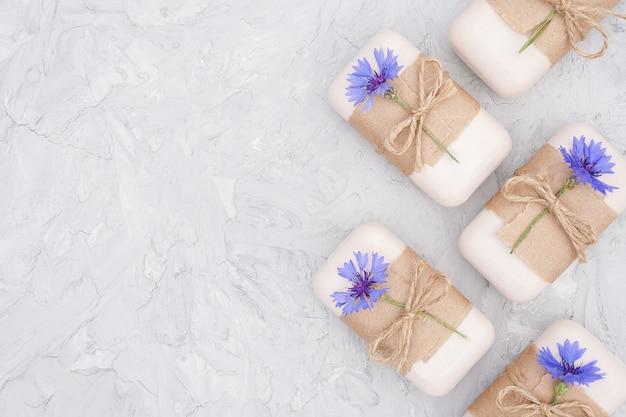Handgemaakte natuurlijke zeep set grens versierd met kraftpapier, plaag en blauwe korenbloemen op grijze stenen achtergrond