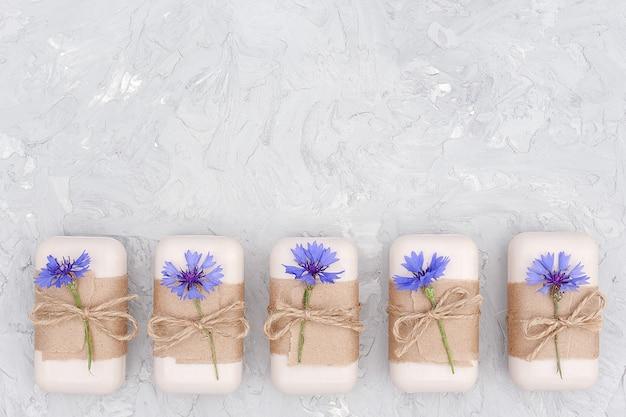 Handgemaakte natuurlijke zeepset versierd met ambachtelijk papier, gesel en blauwe bloemen. biologisch cosmetica concept.