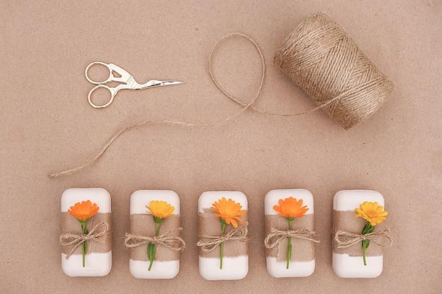 Handgemaakte natuurlijke zeepset versierd met ambachtelijk papier, oranje calendulabloemen, streng van touw en schaar.