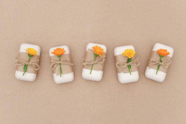 Handgemaakte natuurlijke zeepset versierd met kraftpapier, plaag en oranje calendula bloemen. biologische cosmetica, geen afval,